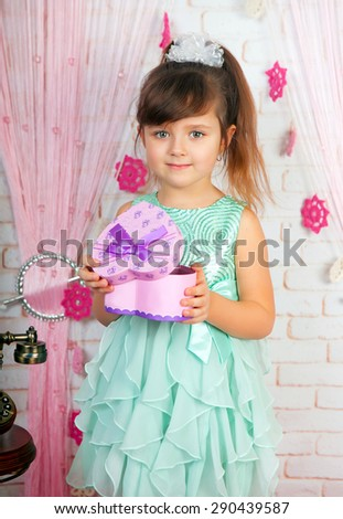 little cute girl in a green dress holding a gift in the scenery