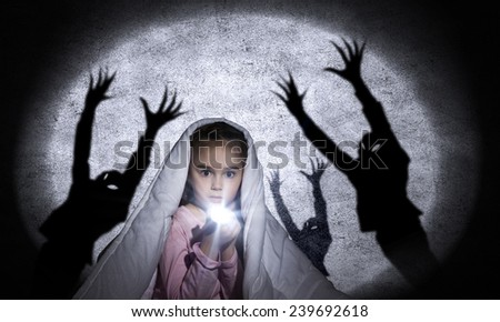 Little cute girl in bed hiding under blanket - stock photo
