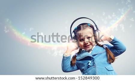 Little cute girl in headphones enjoying music - stock photo