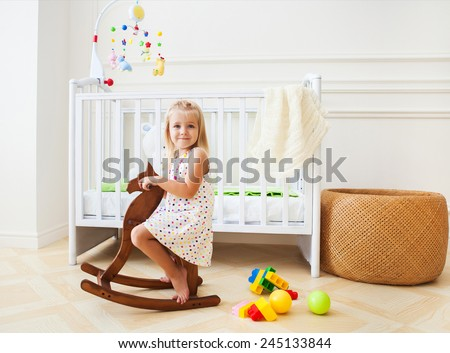 Little cute girl in nursery room with basket, toys and wooden horse - stock photo