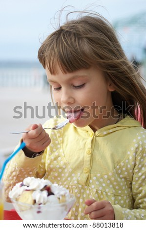 Little cute girl in outdoor cafe. - stock photo