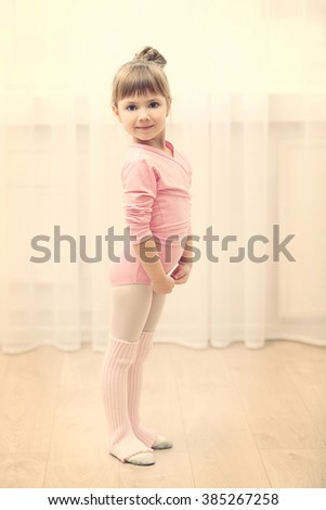 Little cute girl in pink leotard standing at dance studio