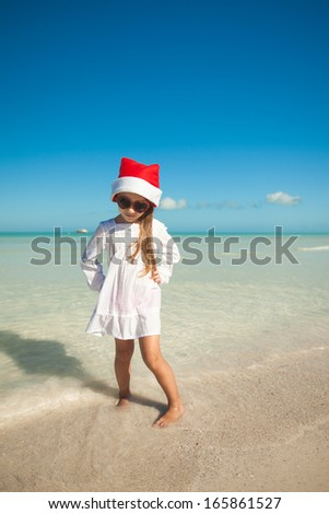 Little cute girl in red hat santa claus and sunglasses on the beach