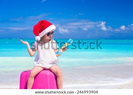 Little cute girl in Santa hat on suitcase at tropical beach - stock photo