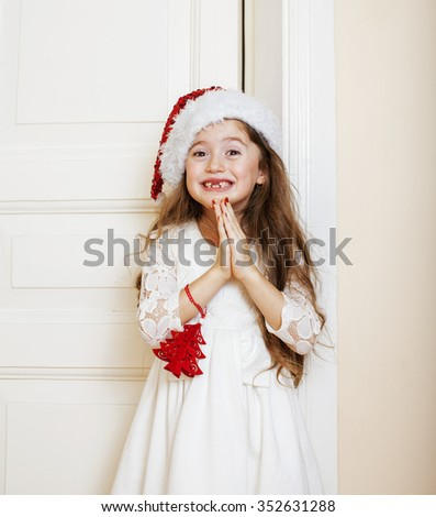 little cute girl in santas red hat waiting for Christmas gifts. smiling adorable kid. White new dress home interior - stock photo