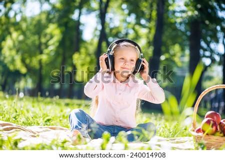 Little cute girl in summer park listening music - stock photo