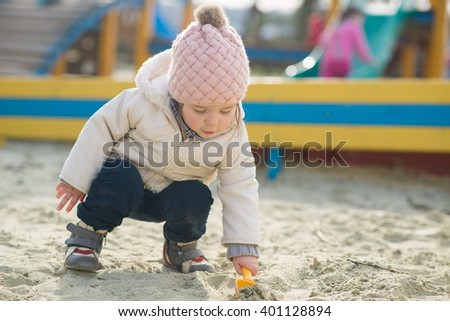 Little cute girl in the sandbox outdoors in the park - stock photo