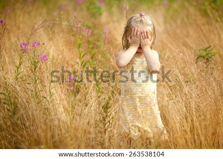 little cute girl in yellow dress is standing in the field and covers face with her hands - stock photo