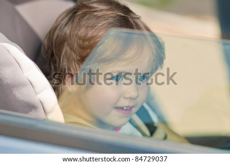 little cute girl kid sitting in safety seat and looking through window pane - stock photo