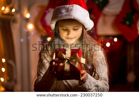 Little cute girl looking inside of glowing Christmas present box - stock photo