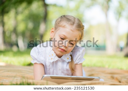 Little cute girl lying in park and using tablet pc