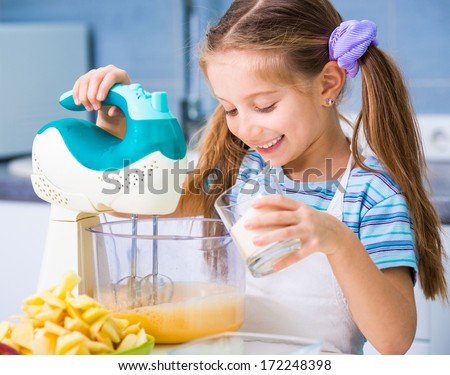 little cute girl making dough for apple pie in the kitchen at home
