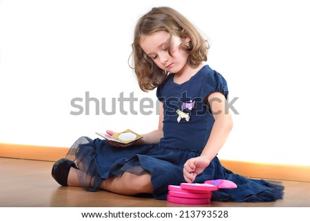 Little cute girl making up while wearing her mother's shoes