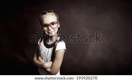 Little cute girl of school age in glasses against blackboard - stock photo