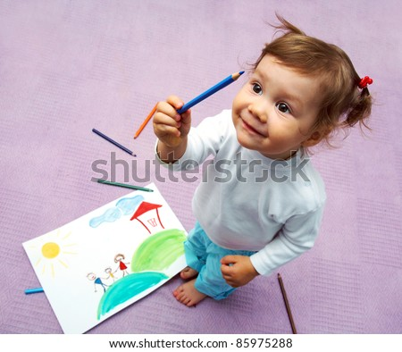 Little cute girl painting her family - stock photo