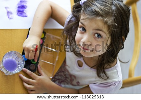 Little cute girl painting with brush inside in preschool. Child care.
