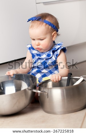 Little cute girl playing in kitchen with pots