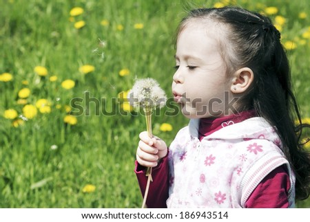 Little cute girl playing on the meadow with dandelions - stock photo