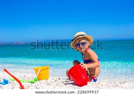 Little cute girl playing with beach toys during vacation