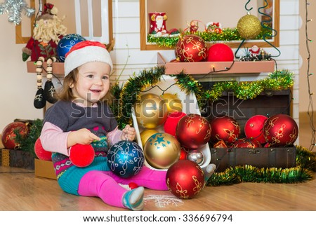 Little cute girl playing with christmas decorations - stock photo