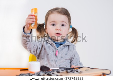 little cute girl playing with cosmetics over the white background
