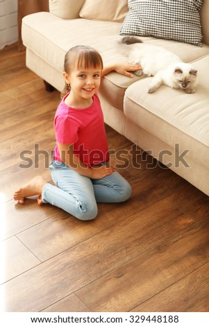 Little cute girl playing with kitten at home