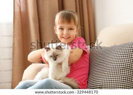 Little cute girl playing with kitten on sofa at home - stock photo