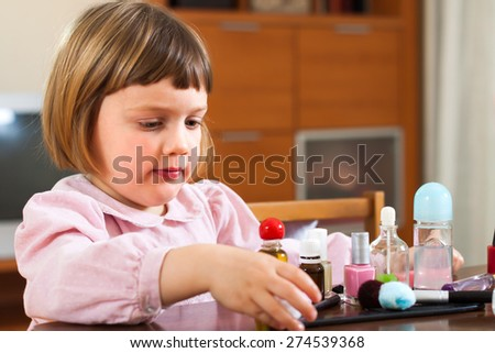Little cute girl playing with makeup - stock photo