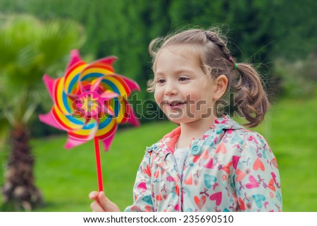 Little cute girl playing with pinwheel outdoors - stock photo