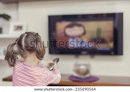 little cute girl pointing remote to control television at home - stock photo
