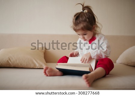 little cute girl reading book at home - stock photo