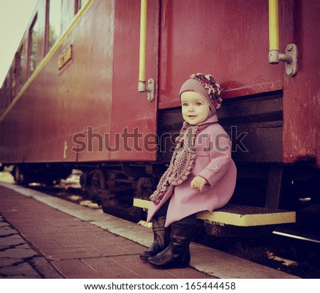 Little cute girl ready to vacation on railway station, baby girl fashion model go on travels, toned - stock photo