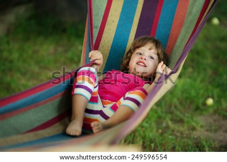 little cute girl resting lying on hammock - stock photo