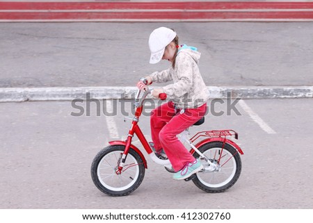 Little cute girl rides red bicycle on asphalt near building at summer day - stock photo