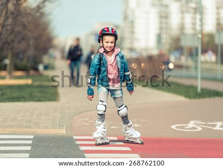 little cute girl riding on roller skates on the bike path - stock photo