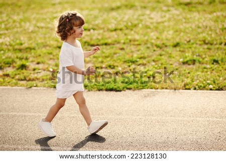 little cute girl running at stadium photo