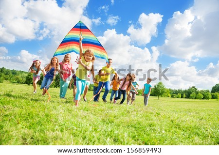 Little cute girl running with kite on a sunny day in the park with many friends in the park