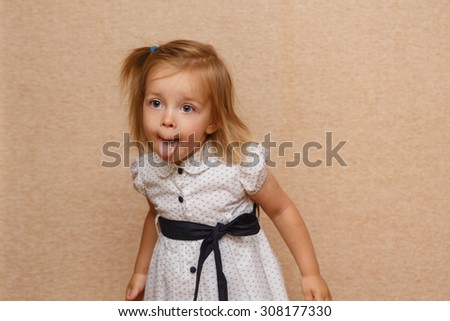 Little cute girl shows tongue. Positive emotions. The concept of carefree childhood. - stock photo