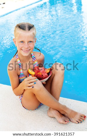 Little cute girl sitting beside the pool with a plate of ripe fruit. Summer