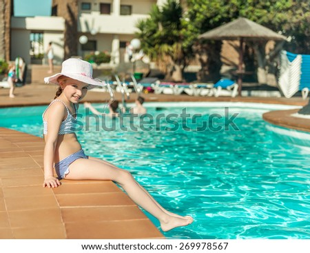 little cute girl sitting near the pool