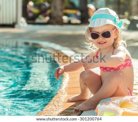 little cute girl sitting near the pool with a circle for swimming - stock photo