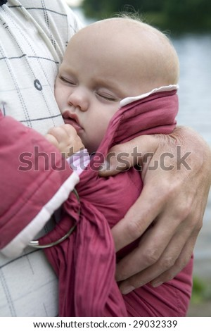 little cute girl sleeping in sling. Father`s hand hold her.  Summer time - stock photo