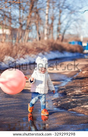 little cute girl two years in a white cap and a jacket with big pink balloon runs on a sunny spring day, the puddles and smiling - stock photo
