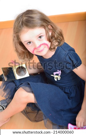 Little cute girl using make-up to turn herself into clown