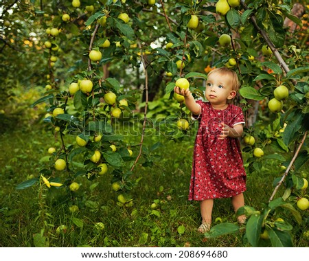 Little cute girl walking barefoot in the garden near the apple tree