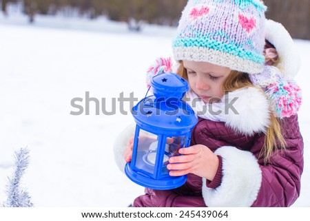 Little cute girl warms her hands on candle in blue lantern in winter time - stock photo