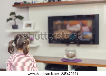 Little cute girl watching television at home - stock photo
