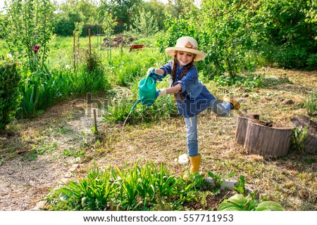 little cute girl watering trees and flowers in the family garden at a summer day