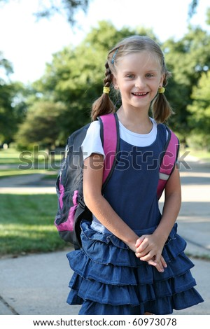 Little cute girl with a big backpack on the way to school.