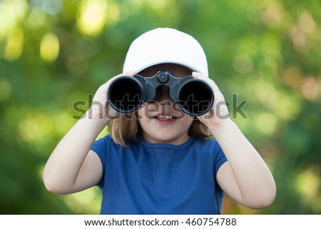 Little cute girl with a cap in the park looking by binoculars